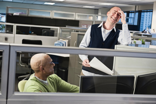 Caucasian male and black male talking and smiling in a cubicle office setting.の写真素材 [FYI02263669]