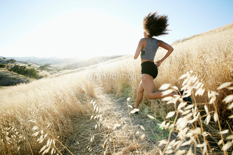 Young woman with curly brown hair running in urban park.の写真素材 [FYI02263675]