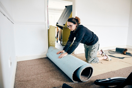 Woman rolling up old carpet in preparation to renew flooringの写真素材 [FYI02263676]