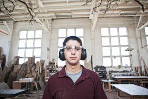 Caucasian man factory worker wearing hearing protection in a woodworking factory.の写真素材 [FYI02263685]