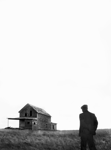 Rear view of man standing in prairie, abandoned farmhouse in the distance.の写真素材 [FYI02263686]