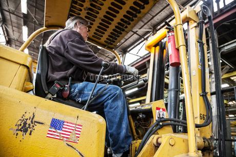 Caucasian man factory worker driving a fork lift in a sheet metal factory.の写真素材 [FYI02263699]