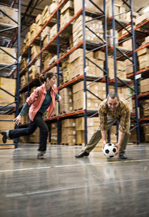 Two warehouse workers playing soccer during a work break in a distribution warehouse.の写真素材 [FYI02263700]