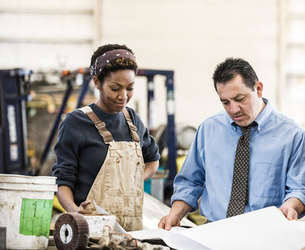 Hispanic man manager and black woman factory worker going over project plans in a sheet metal factorの写真素材 [FYI02263705]