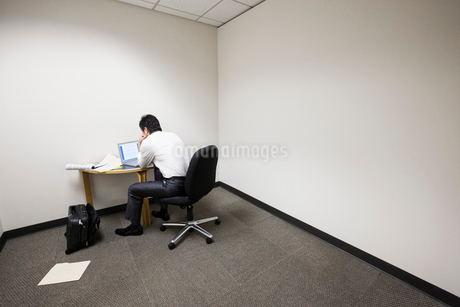 A businessman working alone at a small desk in an empty corner of an office.の写真素材 [FYI02263711]