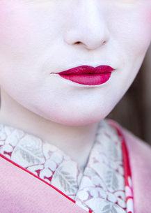 Close up of Geisha's face with traditional make up, pale white skin and bright pink lipstick.の写真素材 [FYI02263720]
