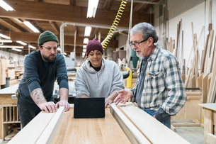 A group of mixed race carpenters discussing a project at a work station in a large woodworking shop.の写真素材 [FYI02263721]