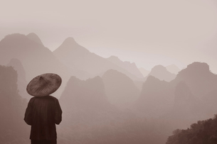 Rear view of man wearing traditional straw hat looking out over mountain range.の写真素材 [FYI02263725]