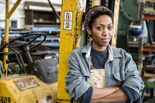 Black woman factory worker and a fork lift in a sheet metal factory.の写真素材 [FYI02263732]