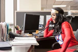 A black office superhero businesswoman takes a call in her office from a client.の写真素材 [FYI02263754]