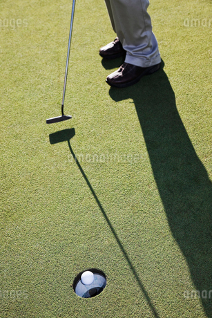 Closeup of golfer hitting a put and a golf ball going into the cupの写真素材 [FYI02263756]