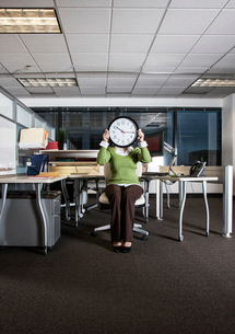 Woman holding a clock face while sitting in her cubicle office space.の写真素材 [FYI02263763]