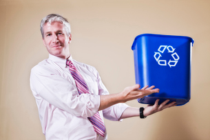 Caucasian man in shirt and tie holding a recycle waste bin.の写真素材 [FYI02263765]