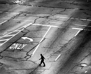 High angle view of man walking across a street junction with several traffic lanes, cracked asphalt.の写真素材 [FYI02263781]