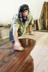 Caucasian man factory worker applying finish to a recycled wood table top in a woodworking factoryの写真素材 [FYI02263782]