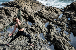 Young woman with brown hair and dreadlocks wearing sportswear standing on rocky shore by ocean, doinの写真素材 [FYI02263784]