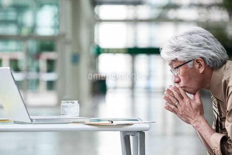 An Asian businessman ponders a problem on his laptop computer at his desk.の写真素材 [FYI02263791]