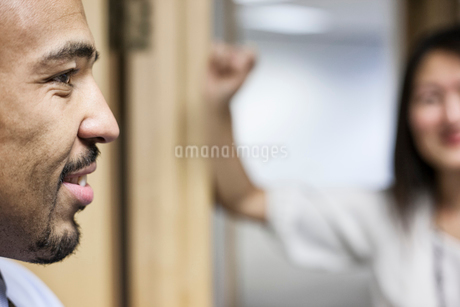 Side view closeup of a black businessman standing and talking in his office space.の写真素材 [FYI02263792]