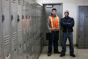 Young Caucasian man and a black man factory worker standing next to lockers in a factory break roomの写真素材 [FYI02263794]
