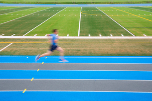 Side view of man running on blue track on sports field, motion blur.の写真素材 [FYI02263797]