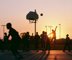 Silhouette of group of men playing basketball at sunset.の写真素材 [FYI02263798]
