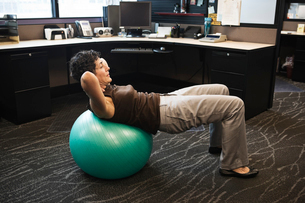 Caucasian woman working out on a Bosu Ball in her office cubicle.の写真素材 [FYI02263800]