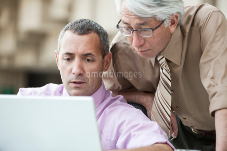 An Asian businessman and Caucasian businessman working on lap top computer in the lobby of a conventの写真素材 [FYI02263806]