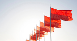 Row of bright red flags on flagpoles fluttering in the wind, clear sky.の写真素材 [FYI02263815]