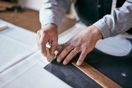 Tailor using chalk and ruler to outline pattern on fabricの写真素材 [FYI02263827]