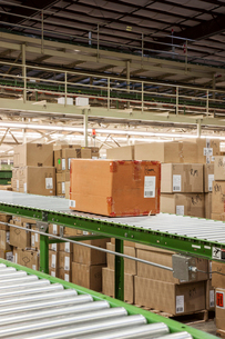 Conveyor belt system and cardboard boxes of products in a distribution warehouse.の写真素材 [FYI02263832]