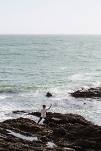 Young woman with brown hair and dreadlocks wearing white blouse standing on rocky shore by ocean, doの写真素材 [FYI02263835]