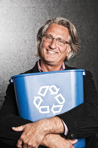 Studio portrait of Caucasian man actor holding a blue recycling bin to his chest.の写真素材 [FYI02263836]