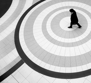 High angle view of man wearing coat and hat walking across tiled floor with circular pattern.の写真素材 [FYI02263842]