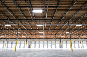 Wide angle interior view of large empty warehouse and loading dock doorsの写真素材 [FYI02263843]