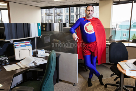 Caucasian middle aged man super hero in his cubicle office.の写真素材 [FYI02263849]