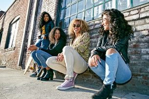 Four young women with curly hair sitting side by side on steps outside a building.の写真素材 [FYI02263856]