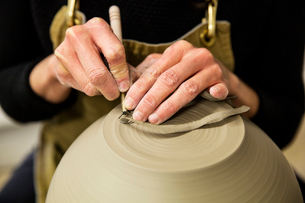 Close up of potter wearing apron working on spherical clay vase on pottery wheel.の写真素材 [FYI02263857]