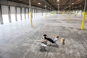 Caucasian man sitting with feet up on desk  in front of loading dock doors in a new warehouse interiの写真素材 [FYI02263872]