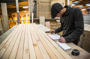 Man wearing flat cap standing at a workbench with wooden planks in a warehouse, holding ruler, writiの写真素材 [FYI02263877]