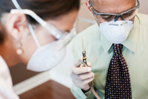 Closeup of a dentist and his assistant working on a patient in a dental office.の写真素材 [FYI02263878]