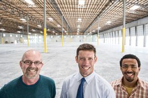 Multi-racial group of men standing in front of loading dock doors in a new empty warehouse.の写真素材 [FYI02263882]