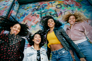 Low angle view of four young women with curly hair standing in front of shutter covered in colourfulの写真素材 [FYI02263887]