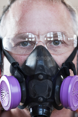 Close up view of Caucasian man factory worker wearing safety glasses and respirator.の写真素材 [FYI02263903]