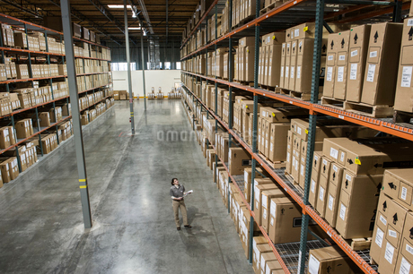 A view from above looking down on a warehouse worker checking inventory of boxes on racks in a distrの写真素材 [FYI02263906]