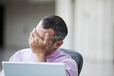 A Caucasian businessman pondering a problem while working on a laptop computer.の写真素材 [FYI02263908]