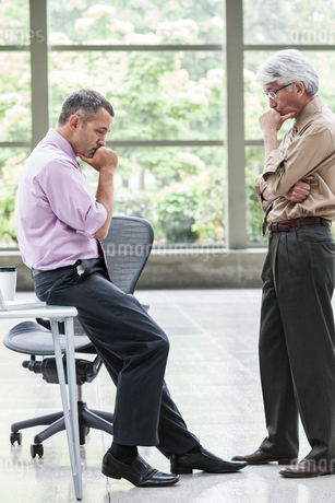 A Caucasian businessman and an Asian businessman ponder a question together.の写真素材 [FYI02263910]