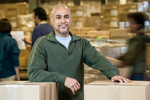 A portrait of a black warehouse business manager. surrounded by storage boxes and employees.の写真素材 [FYI02263911]