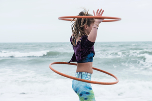 Young woman with brown hair and dreadlocks standing by the ocean, balancing two hula hoops.の写真素材 [FYI02263912]