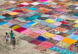 High angle view of three children standing on a field with a large number of colourful cotton fabricの写真素材 [FYI02263913]