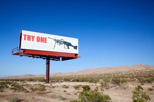 Large board advertising machine gun in the desert.の写真素材 [FYI02263914]